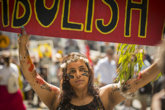 A woman carries a sign calling for the abolition of Australia Day while taking part in a 2019 Invasion Day march in Melbourne.