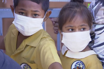 Masked children wait to get vaccinated at a health clinic in Apia, Samoa. Samoa has closed all its schools and banned children from public gatherings due to a measles outbreak.