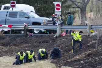 Royal Canadian Mounted Police investigators search for evidence at one of the shooting scenes.