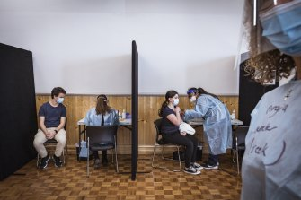 Panos Menidis, aged 20, and Kanella Pirpiris, aged 16, their vaccine in a church hall on Sunday.