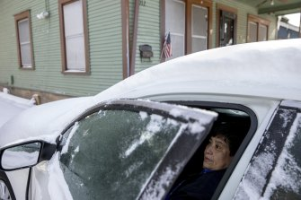 Maria Pineda warms up in her car outside her home in East Austin, Texas, during a power outage caused by the snow storm last week.