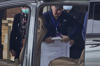 WHO mission member Peter Daszak  rolls up a vendors layout map of Huanan Seafood market as he prepares to leave his hotel for the airport at the end of the probe's trip to Wuhan.
