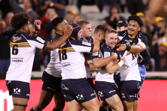 Ryan Lonergan is mobbed by Brumbies teammates after his match-winning kick.