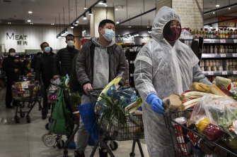 Residents wear protective gear as they line up in a supermarket in Wuhan.