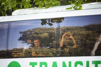 "Mostafa ""Moz"" Azimitabar (right) makes a heart symbol as he is taken by bus away from the Park Hotel."
