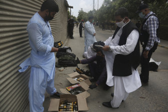 Security personnel examine confiscated ammunition from attackers outside the stock exchange.