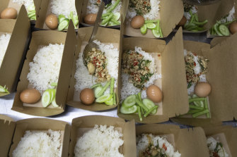 """""""Pad krapow gai"""",  the spicy minced chicken is filled in a box by volunteers at COVID Thailand Aid in Bangkok."""