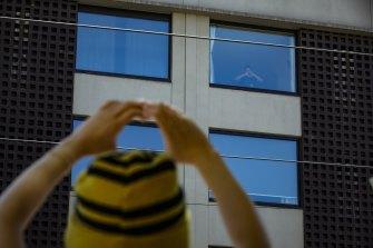 A Bangladeshi refugee signals 'joy' to protestors outside a Carlton hotel.