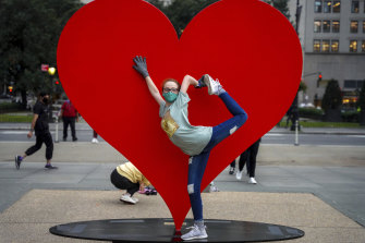"""Jada Cathcart, 16, poses for a picture in front of """"The Hero Monument"""" in New York by Italian sculptor Sergio Furnari, a symbol of hope and love dedicated to healthcare workers around the world."""