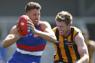 Marcus Bontempelli of the Bulldogs is tackled by Hawthorn's Ben McEvoy.