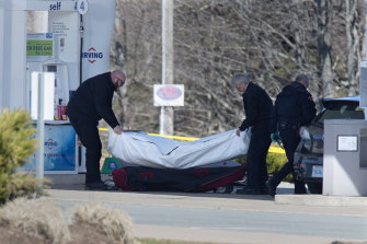 Workers with the medical examiner's office remove a body from a petrol station in Enfield, Nova Scotia, on Sunday.