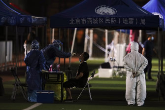 Medical staff test a person for COVID-19 near the Xinfadi Market in Beijing.
