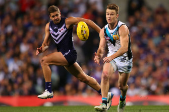 Robbie Gray of the Power handballs against Stephen Hill of the Dockers.