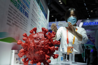 An employee displays a coronavirus vaccine candidate from China National Biotec Group (CNBG) at a trade fair in Beijing last month.