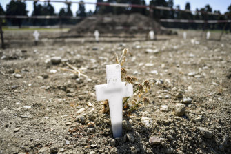 White crosses delimiting the areas for new burials are scattered at the Maggiore cemetery in Milan. The country's death toll topped 25,000 this week.