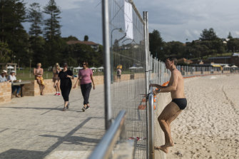 A man jumps the fence at Bronte beach to confront a photographer.