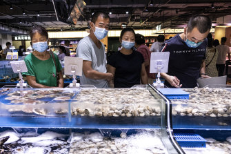 Masked market-goers in Wuhan, China. Authorities are trying to head off an outbreak of the scale seen in the central China city early last year.