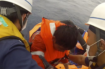 A crew member of a cargo ship is rescued by Japanese Coast Guard members off the Amami Oshima, Japan, on  Friday.