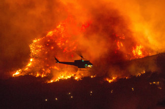 A helicopter prepares to drop water at a wildfire in Yucaipa, California, in September. The UN says the number of natural disasters has doubled this century.