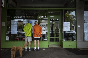 Local residents read a message about the coronavirus and the cafe's dealings with DHHS on the window of The Guilty Moose cafe in Albert Park.