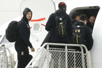 Dustin Martin and Richmond teammates board a flight at Melbourne airport on Monday.
