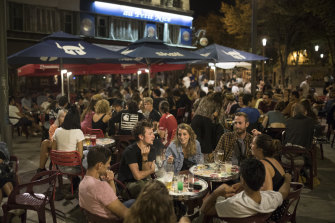 Friends have a drink together at a bar in Marseille, southern France, on Saturday, September 12, as new daily cases of COVID-19 passed 10,000 for the first time.