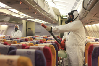A worker sprays a Thai Airways aircraft. Thailand is opening up to tourists from China.