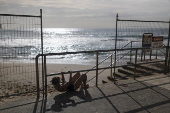 Some would not be deterred from their morning swim despite health warnings and physical barriers at Bronte Beach.