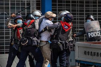 Polisi anti huru hara menangkap pengunjuk rasa anti-kudeta di Myanmar pada bulan Februari. Lebih dari 3.500 masih dalam tahanan polisi, lebih dari 750 tewas oleh tindakan keras militer terhadap pengunjuk rasa.