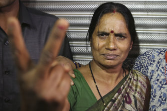 Asha Devi, mother of the victim of the fatal 2012 gang rape on a moving bus, displays a victory sign after the rapists of her daughter were hanged, in Delhi.