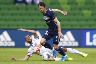 Robbie Kruse, right, and Ivan Franjic, left, contest the ball.