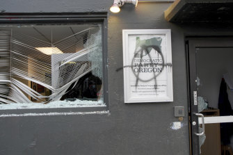 Protesters tag and smash windows at the Democratic Party of Oregon headquarters on Wednesday, January 20, in Portland.