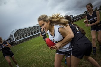 Sports researchers and a growing numbers of female AFL players, including Francesca, Abby, Piper, (getting tackled) Sofia, Jasmine and Grace from the Caulfield Grammar firsts team, and parents are arguing for more awareness of breast protection on the field.
