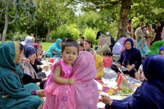 New beginning: Hazara women and children enjoy lunch the men cooked at Footscray Park.