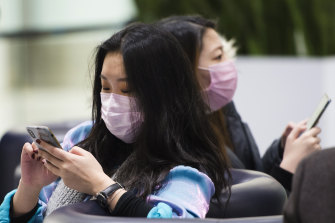 People wear masks at the International terminal at Toronto Pearson International Airport on Saturday, as it emerged the coronavirus had spread to Canada.