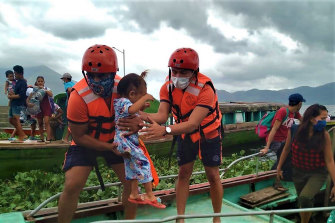 Members of the Philippine Coast Guard carry a child as they are evacuated to safer ground in Camarines Sur province, eastern Philippines as they prepare for Typhoon Goni.
