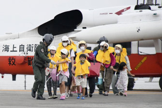 Residents of the islands arrive at a heliport in Kagoshima, southern Japan, to take refuge ahead of a powerful typhoon.
