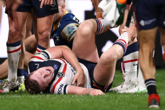 Drew Hutchison of the Roosters writhes in pain. He was sent to hospital with suspected broken ribs.