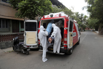 Izhaar Hussain Shaikh, left, picks up a COVID-19 patient from his home in Mumbai, India.