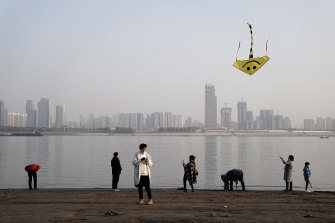A man flies a kite as people walk along the coast of the Yangtze River at Jiangtan park in Wuhan.