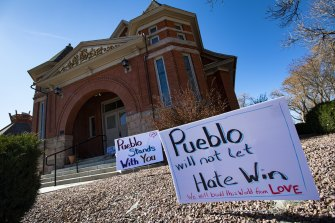 Signs, flowers and candles expressing love for the Jewish community stand outside the Temple Emanuel in Pueblo, Colorado after news of the threat emerged in July 2020.