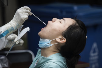 A medical worker takes a swab from a Wuhan resident, part of a drive to test 6.5 million people.
