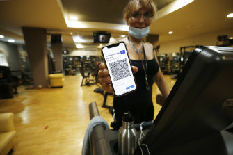 """A customer shows her """"green pass"""" inside a gym in Rome."""