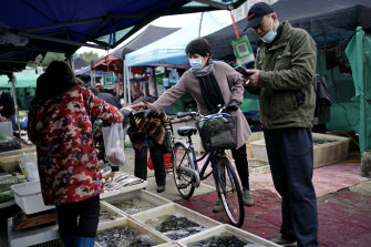 Vendors selling fish in an open market in Wuhan, China, a year after the start of the pandemic.