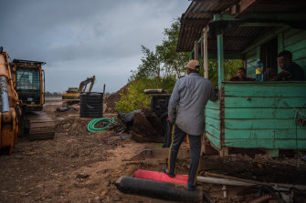 Workers wait for a storm to pass before continuing to repair a breached sea wall in Mahaicony, Guyana.