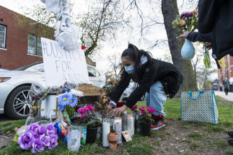 A woman tends to a memorial for Adam Toledo in Chicago.
