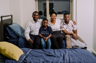 Tanitoluwa Adewumi, 8, his brother, Austin, and their parents, Kayode and Oluwatoyin, in the apartment they obtained after a GoFundMe drive raised more than $US200,000 on their behalf.