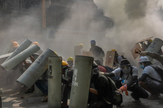 Protesters defend themselves with makeshift shields during clashes with riot police on Sunday.