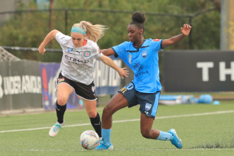 Ellie Carpenter and Princess Ibini battle for the ball at Cromer Park on Sunday.