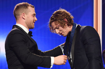 Tom Mitchell presents Nat Fyfe with the 2019 Brownlow Medal.
